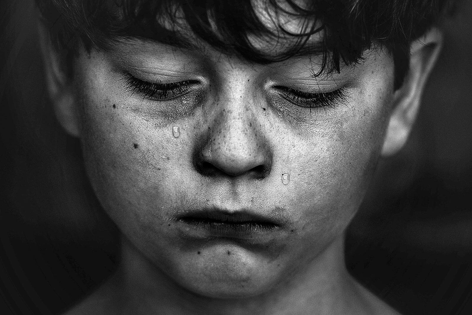 Criança de olhos semi-serrados, com lágrimas a correr pelo rosto.