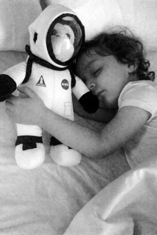 Criança a dormir junto a um peluche astronauta.