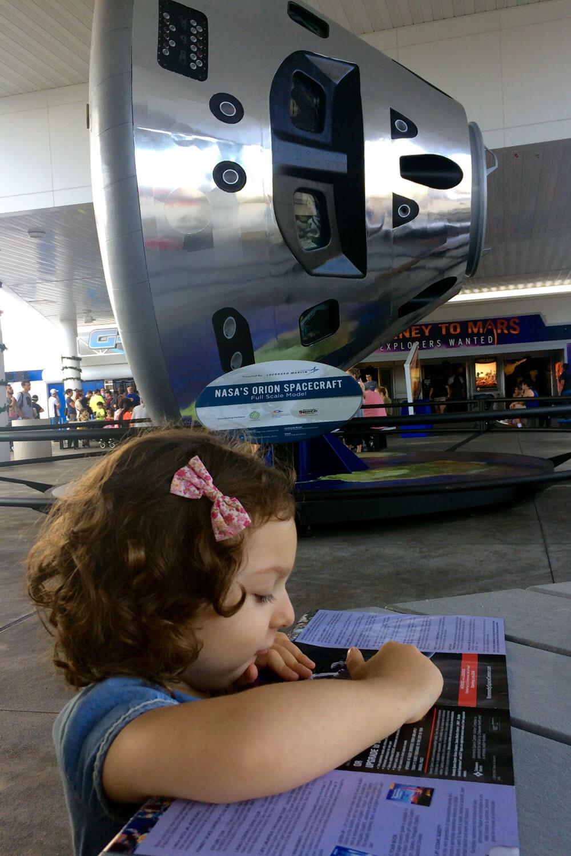 Criança a ler um painel informativo num centro de visita da Nasa.