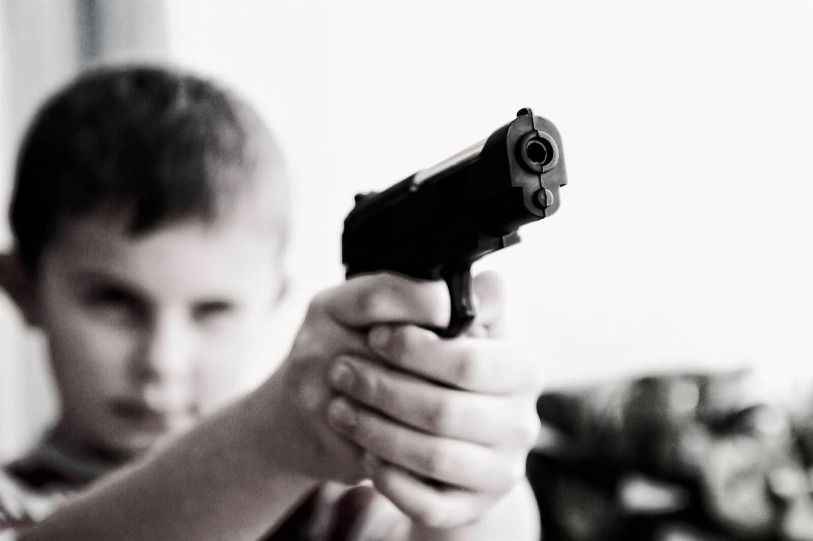 Criança a apontar uma pistola.