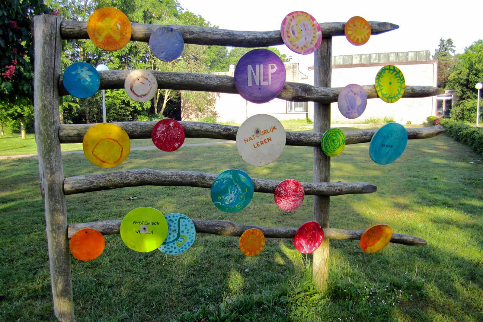 Círculos coloridos, ligados à temática da PNL, afixados sobre estrutura de madeira, num jardim.