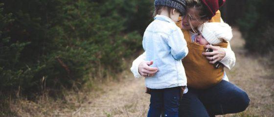 Mulher a abraçar duas crianças num caminho de um bosque.