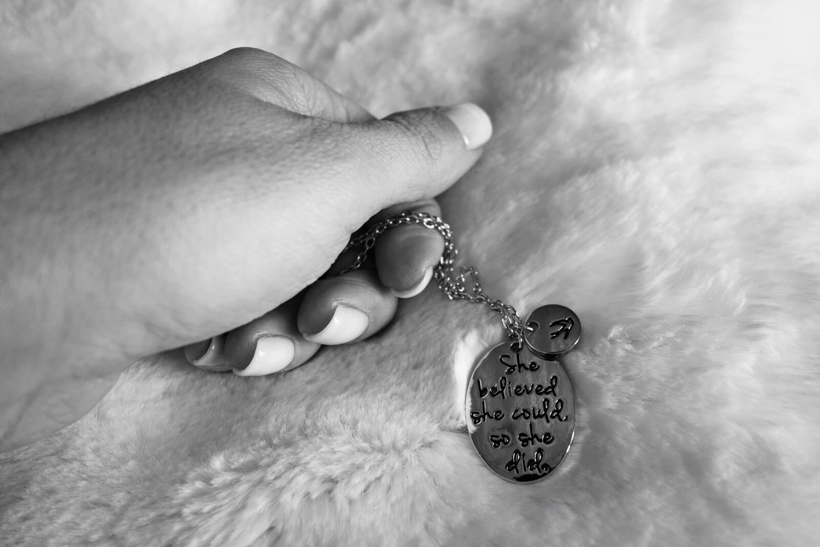 Mão a segurar uma corrente com uma medalha, sobre um cobertor de pelo.