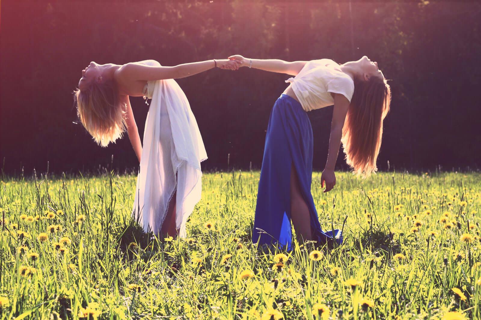 Raparigas de mão dada, num prado florido, um símbolo de educar com liberdade.