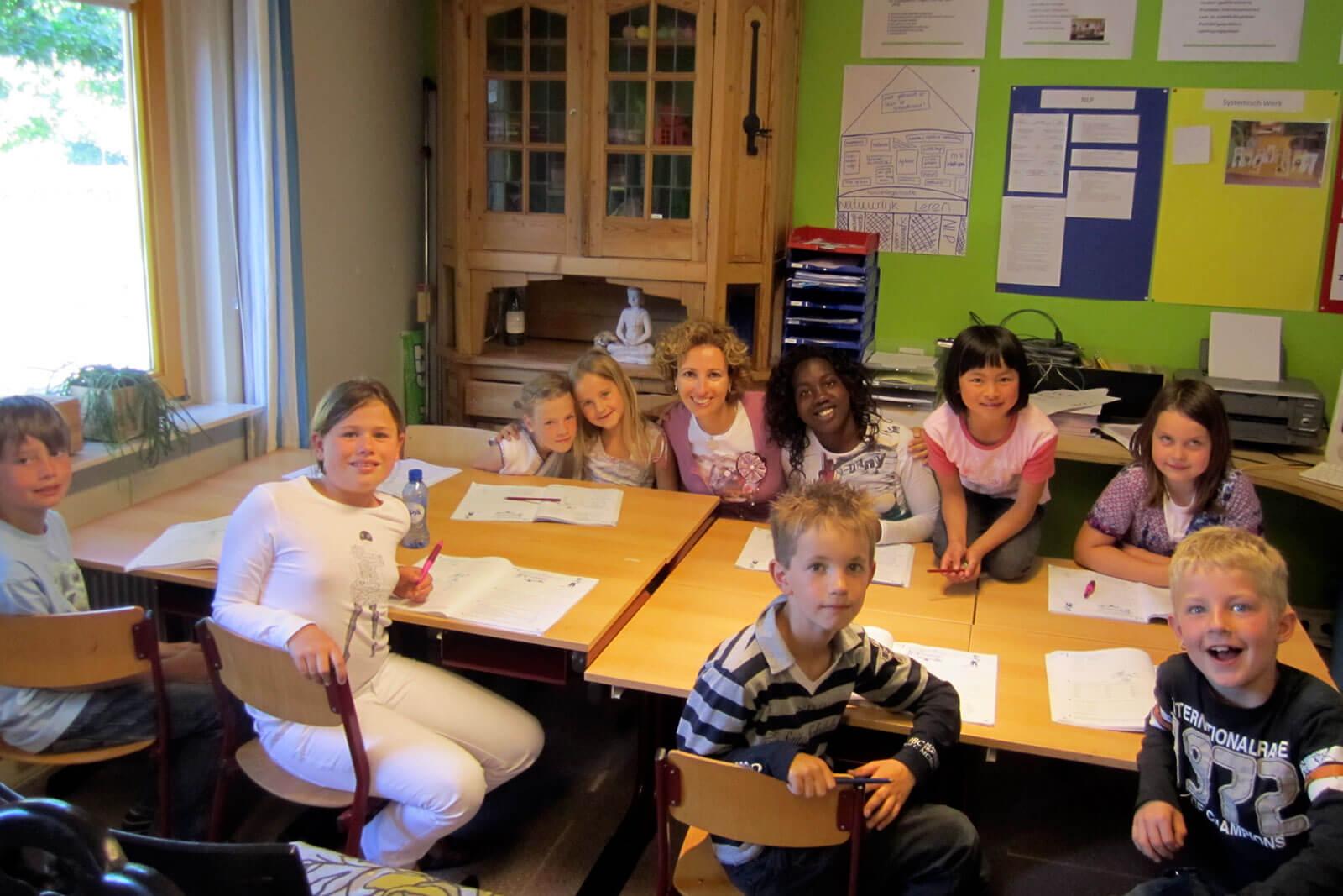 Rita Aleluia com crianças dentro de uma sala de aulas.