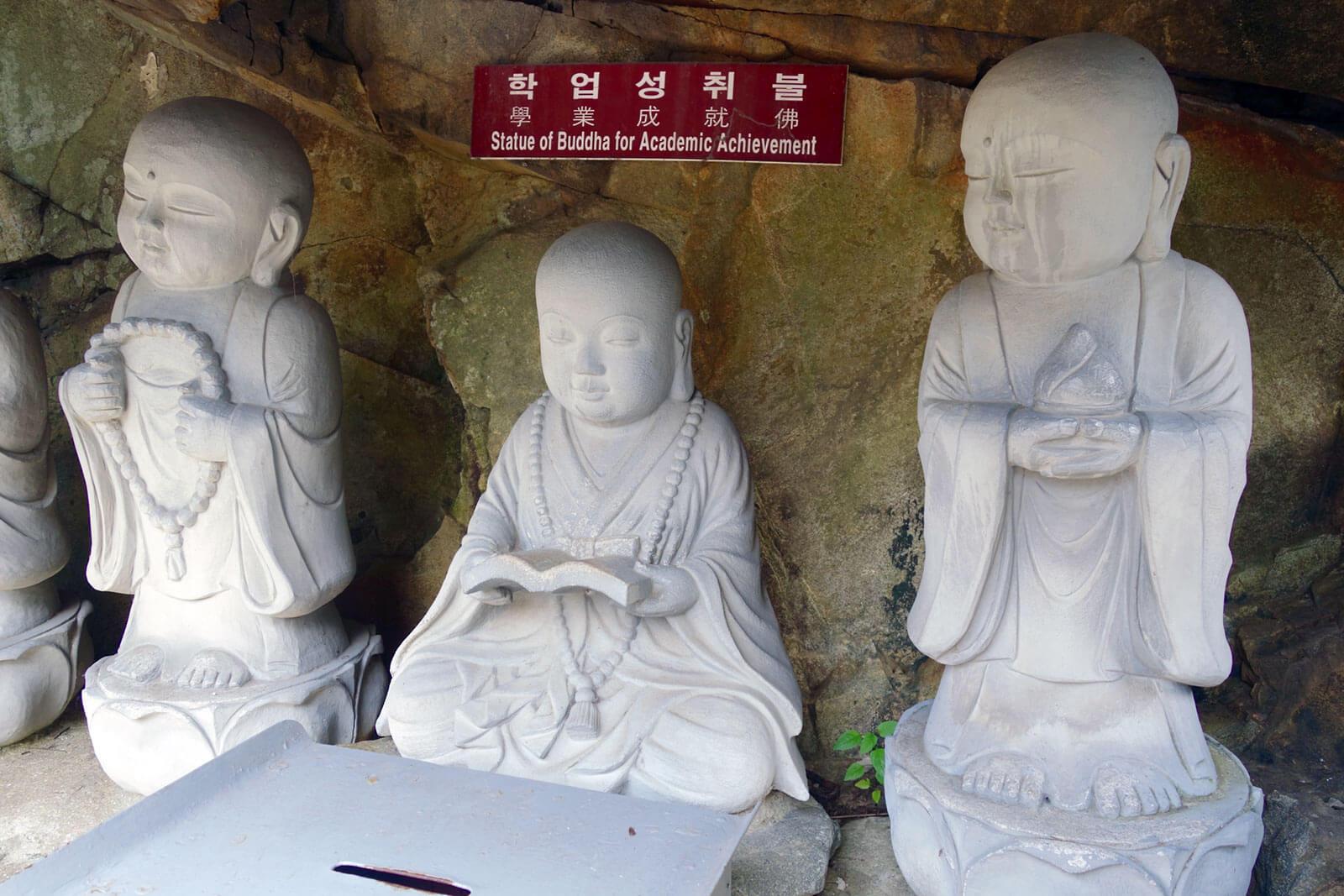 Estátuas de budas em pedra branca, dentro de uma gruta.