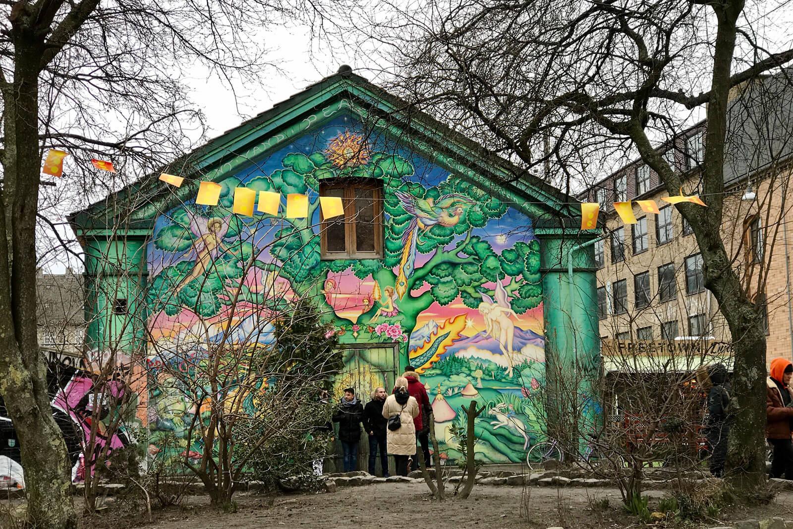 Pessoas junto a um edifício revestido a grafittis, instalado junto a um jardim.