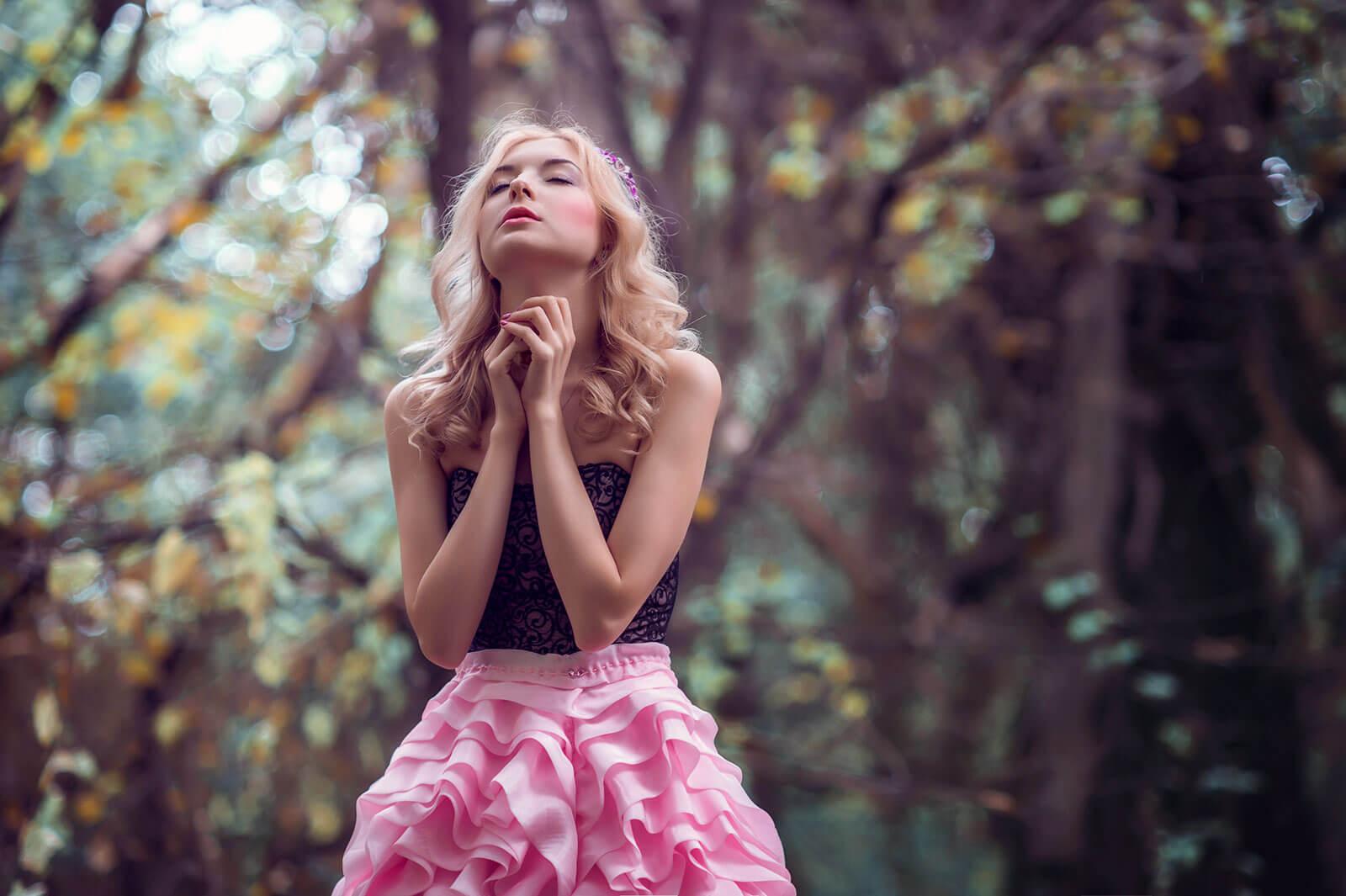 Rapariga de vestido cor-de-rosa numa floresta.