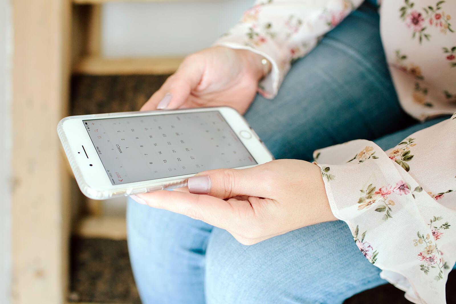 Rita Aleluia sentada numa escada de mandeira com smartphone nas mãos