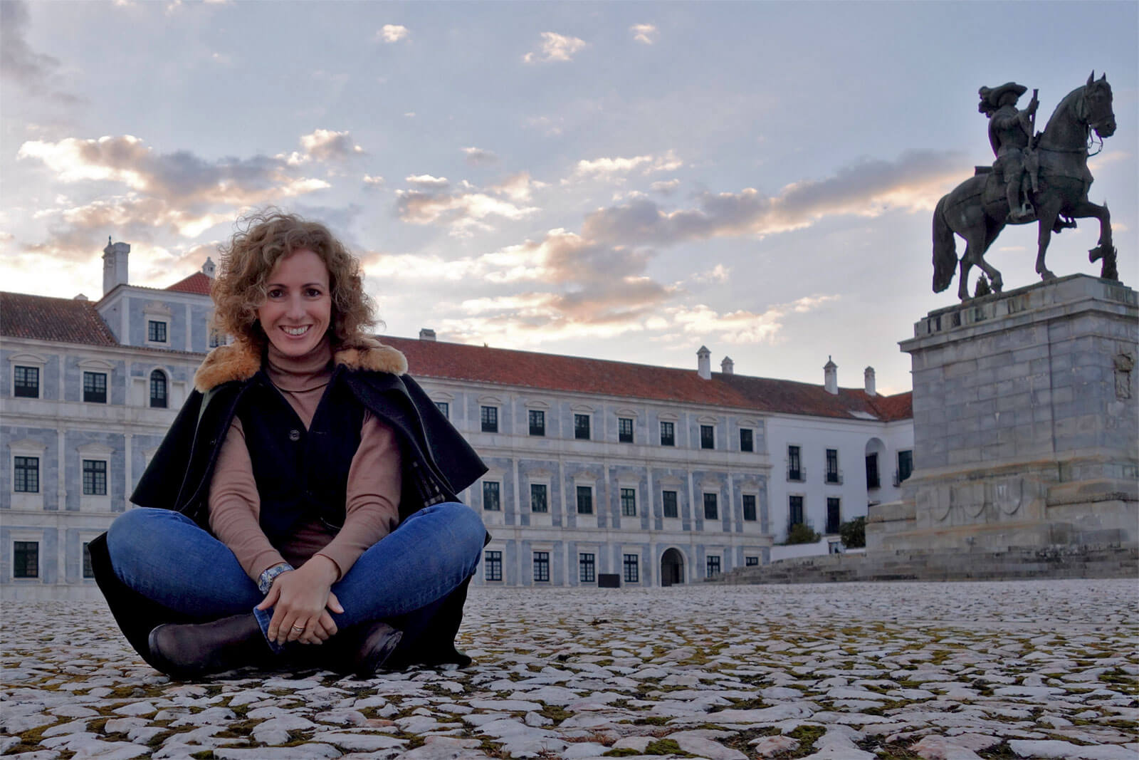 Rita Aleluia sentada numa grande praça, com pavimento em pedra rústica e grande estátua de cavaleiro.