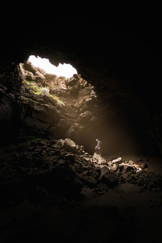 Raios de luz a incidir sobre homem no interior de uma gruta.