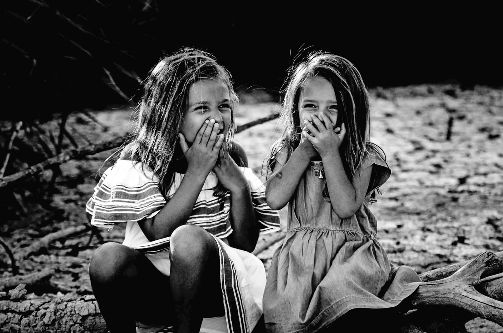 Duas meninas divertidas, sentadas sobre um tronco de árvore no chão.