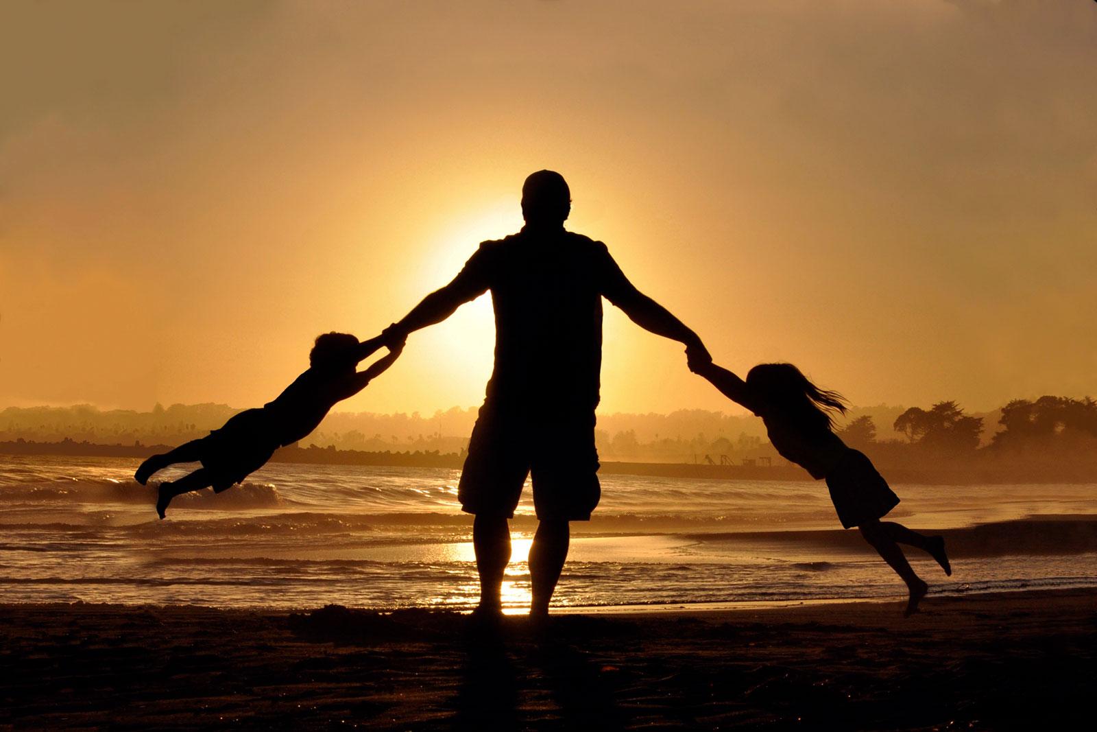 Pai com filhos a rodopiar numa praia, ao pôr-do-sol.