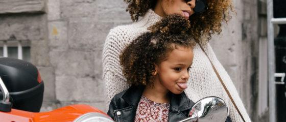 Mulher e criança, de raça africana, com a língua de fora, sentadas numa motorizada de cor laranja.