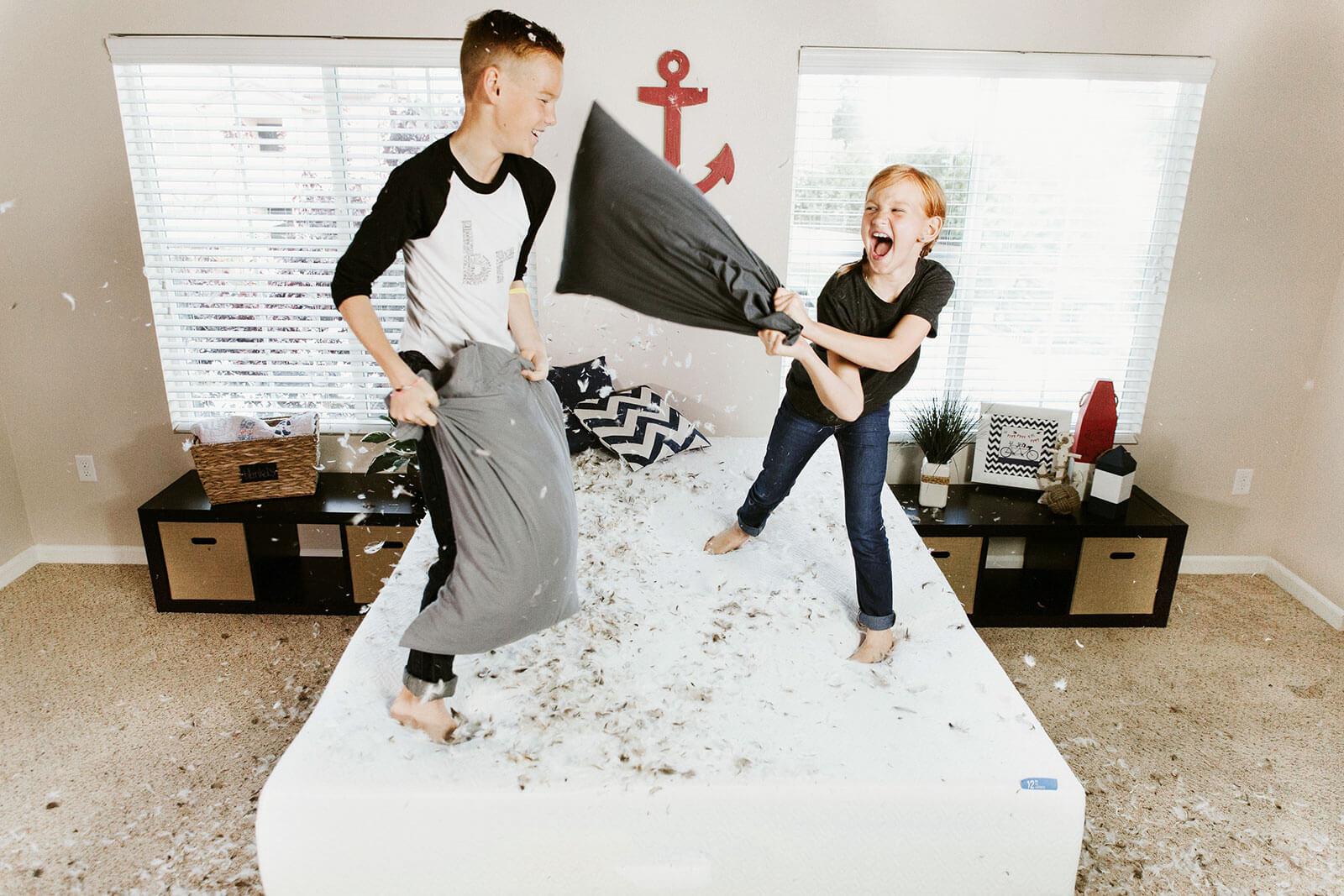 Crianças numa guerra de almofadas de penas, a saltar sobre uma cama.