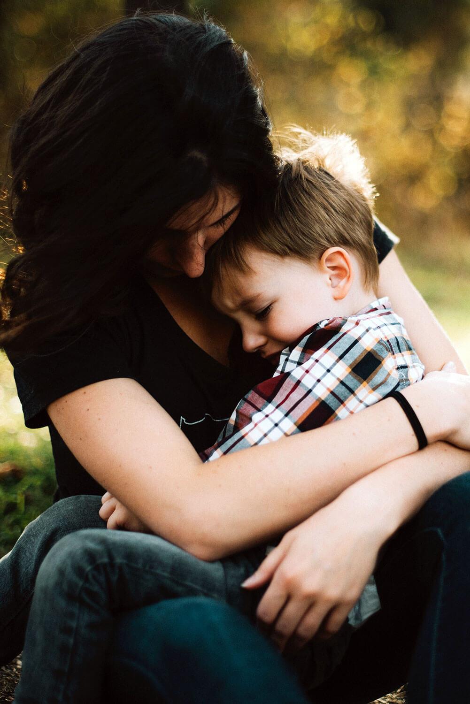 Mãe abraçada ao filho que está ao colo