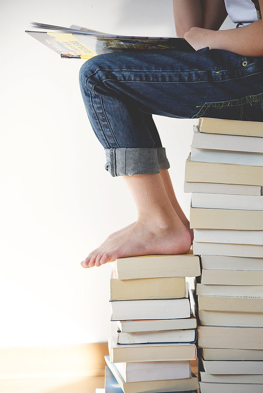 Pessoa sentada sobre um torre de livros