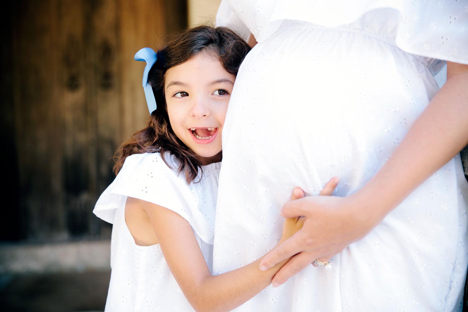 Criança a abraçar mulher grávida com vestido branco.