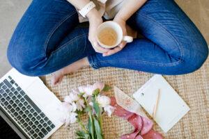 Mulher de pernas cruzadas a segurar numa chávena de café, junto a computador portátil e flores.