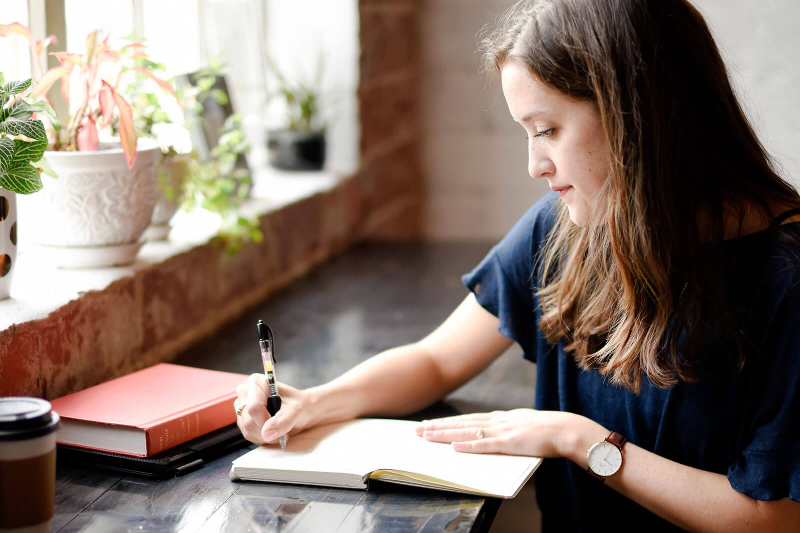 Rapariga a escrever num caderno, sobre uma mesa junto a uma janela.