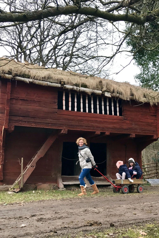 Puxar um carrinho de rodas com crianças, num caminho de terra, frente a uma grande casa de madeira, pode fazer parte de um actividade de PNL e Educação.