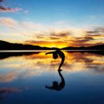 Mulher a fazer Yoga, numa praia ao pôr-do-sol