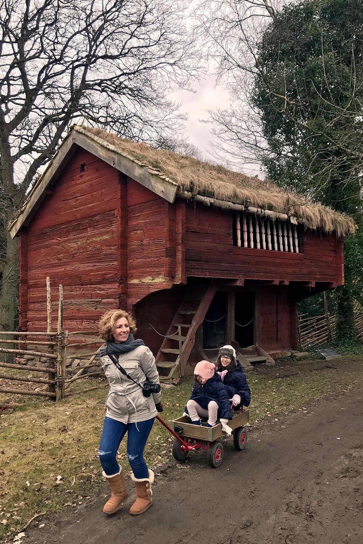 Rita Aleluia a puxar duas crianças dentro de um carrinho de madeira.