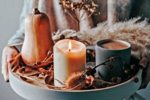 Mulher a segurar num tabuleiro com velas e flores secas.