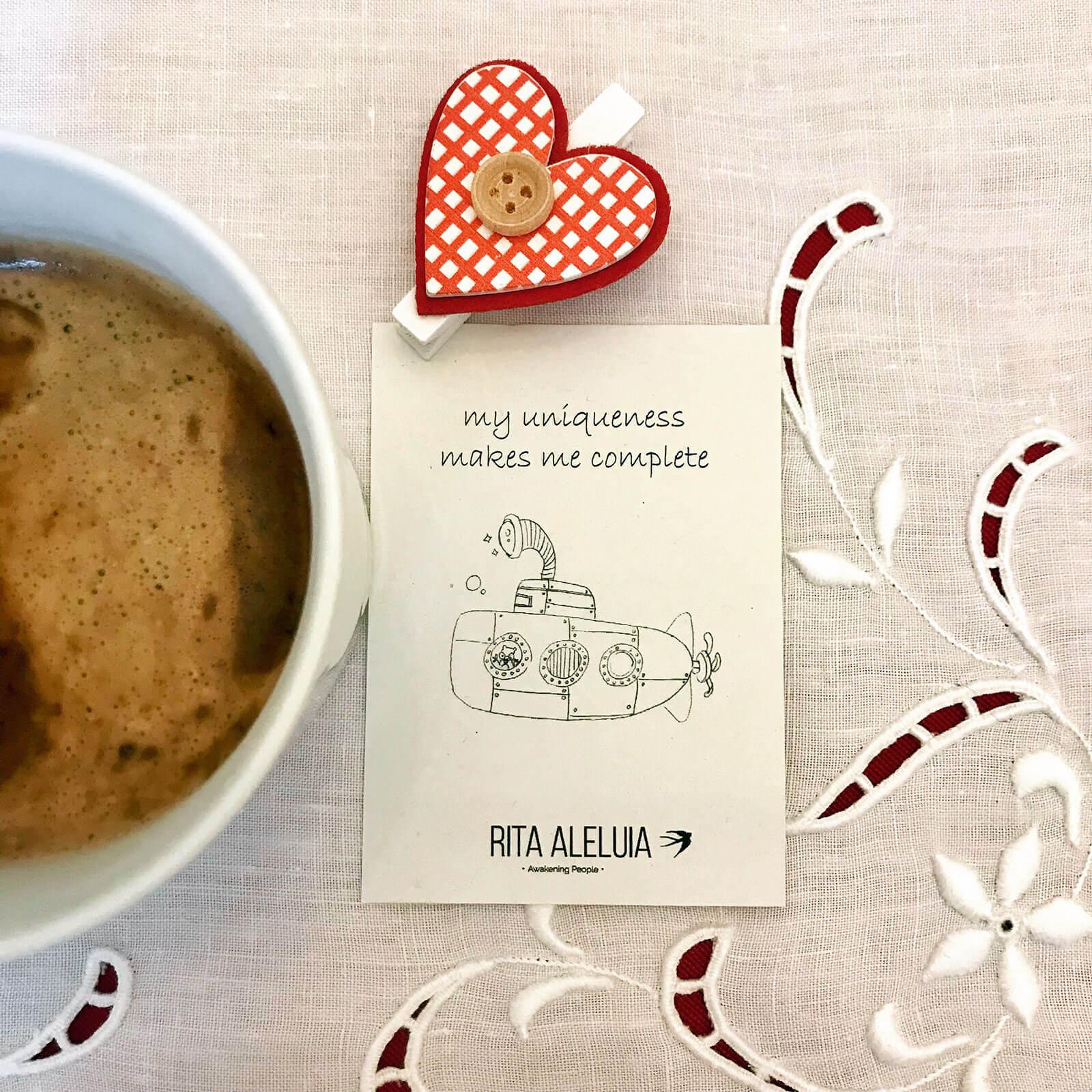 Chávena de café, coração e cartão da Rita Aleluia sobre toalha de mesa.