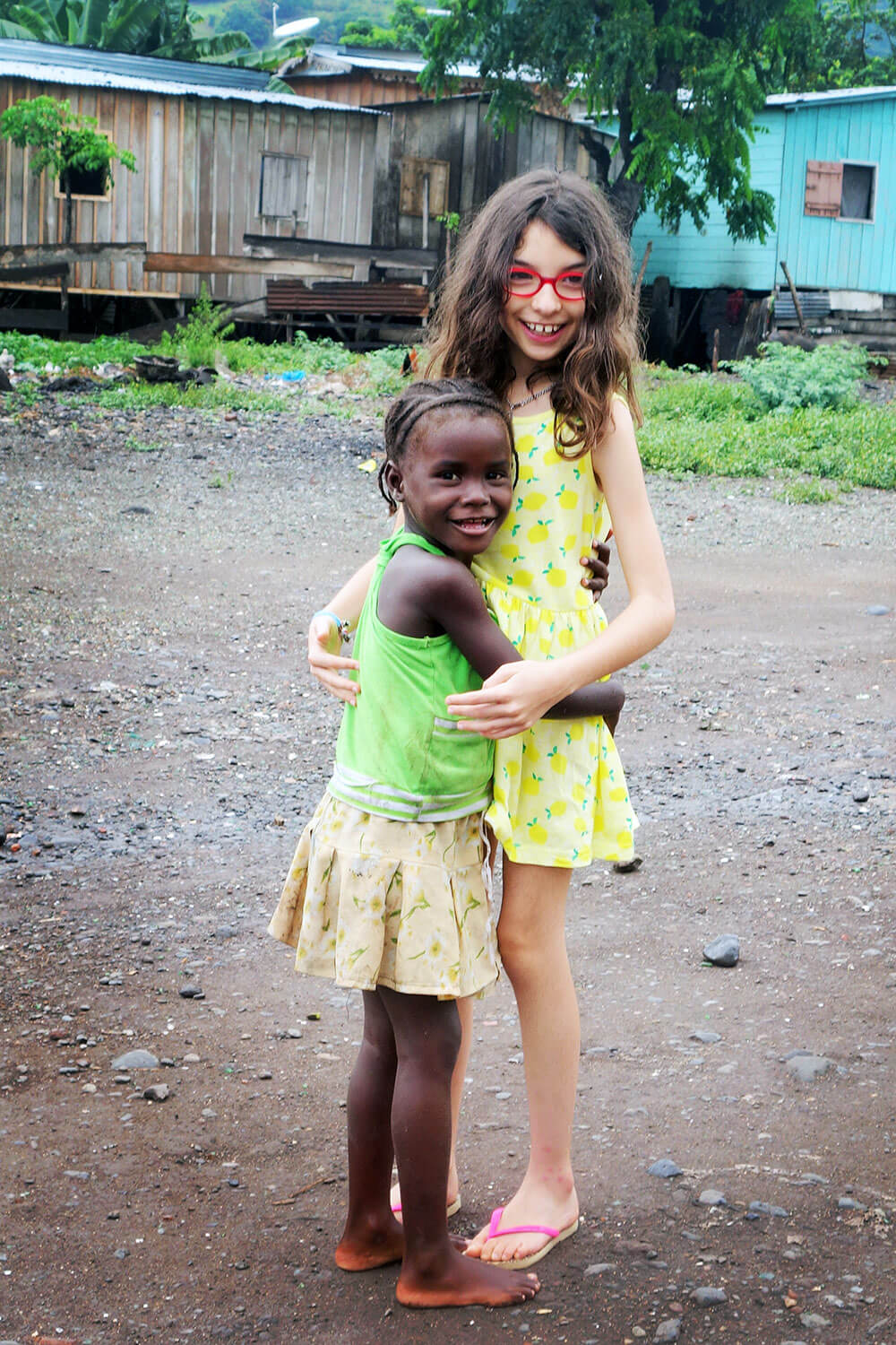 White girl embraces an African child.