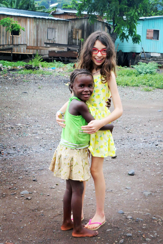 Menina branca a abraçar criança africana.