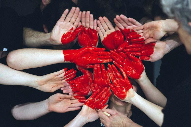 Mãos e braços juntos, com coração gigante pintado de vermelho