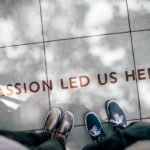 """Pés sobre passeio, na rua, junto a inscrição """"Passion led us here"""""""