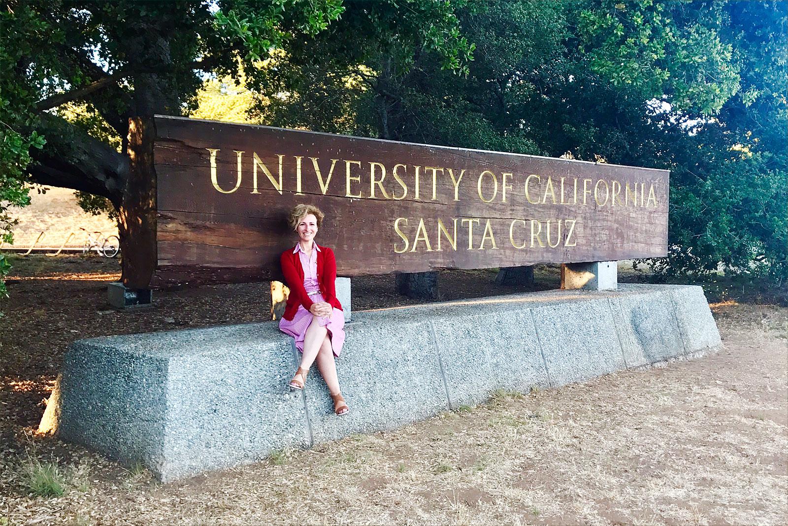 Rita Aleluia sentada junto identificador Universidade Santa Cruz, na California