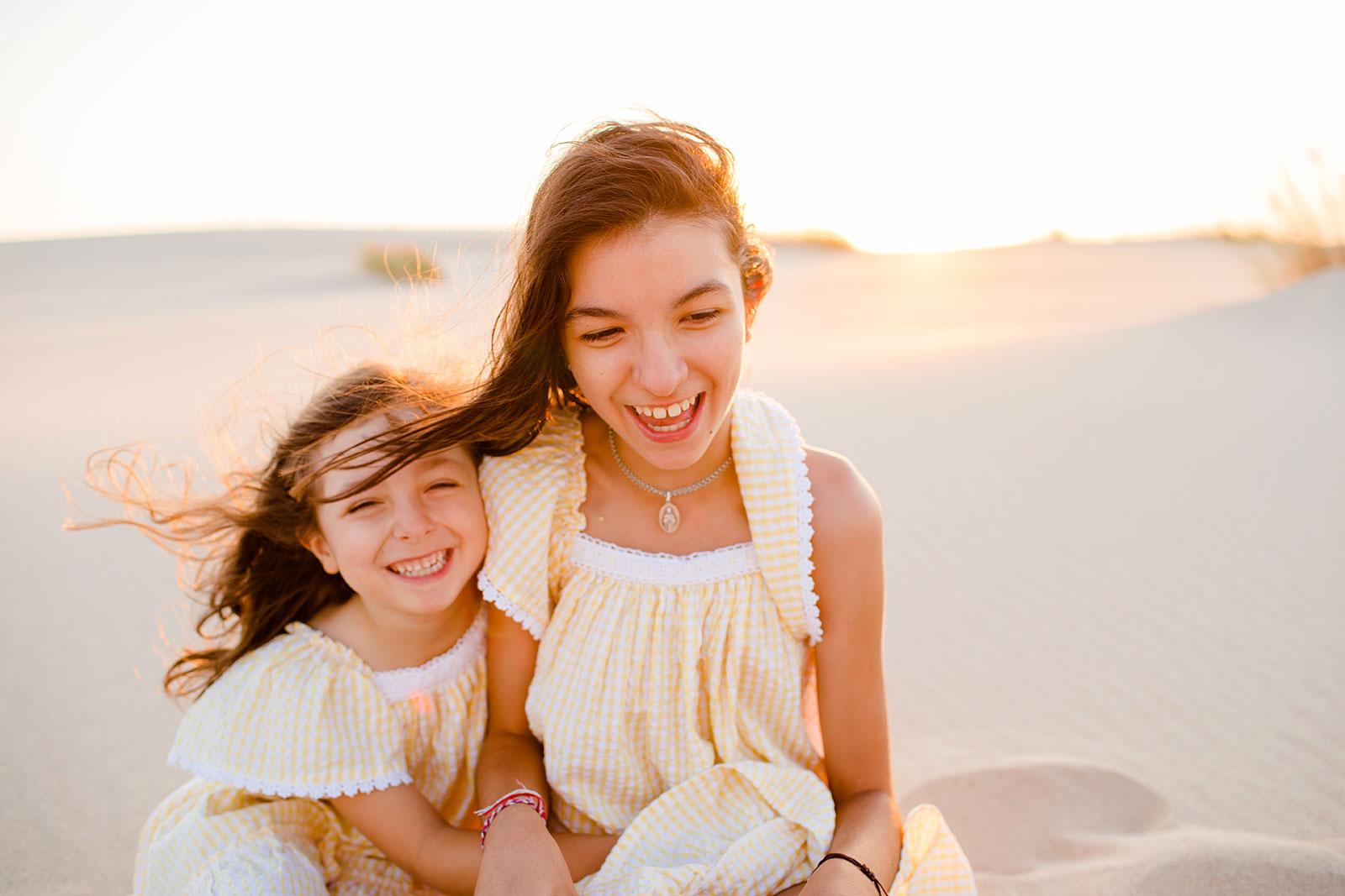 Meninas numa praia ao pôr-do-sol