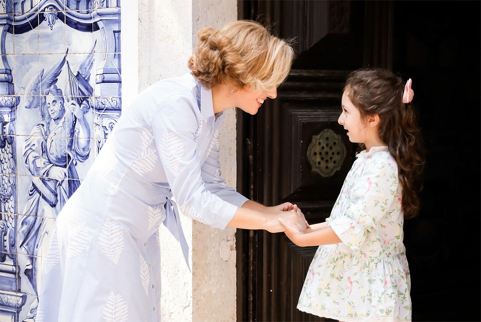 Rita Aleluia de mãos dadas com menina à entrada de uma igreja