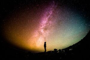 Silhueta de pessoa no campo, sobre paisagem com estrelas da via láctea.