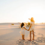 Crianças de mãos dadas numa praia ao pôr-do-sol