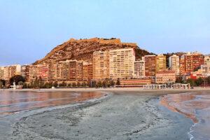 Linha de prédios urbanos entre praia e monte circundado por muralha, na cidade de Alicante.