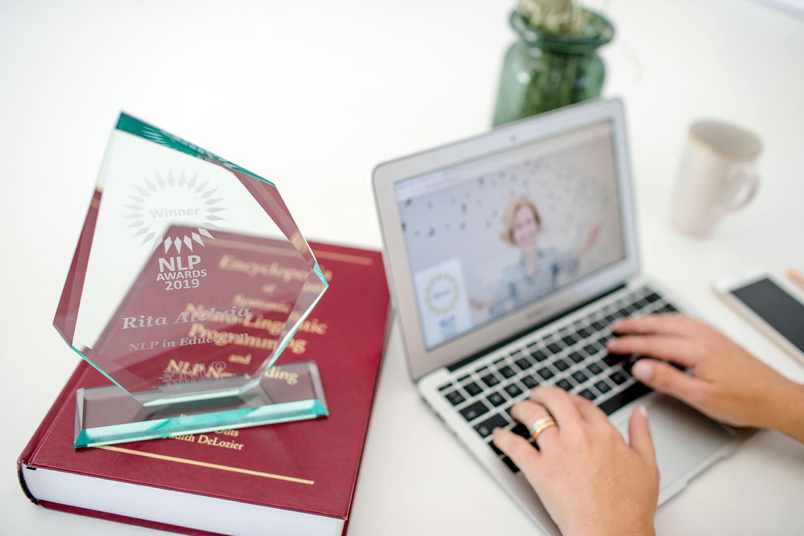 Computador, enciclopédia PNL e prémio PNL 2019 para educação sobre secretária
