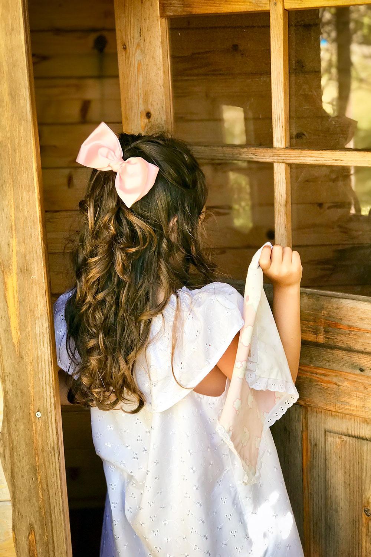 Criança de costas, com laço na cabeça, a abrir porta de uma casa de madeira.