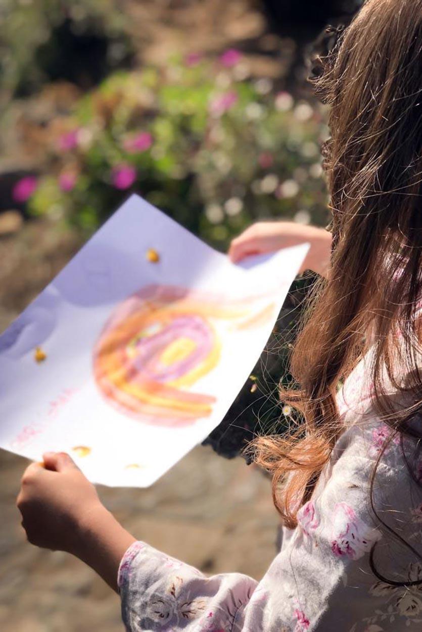 """Criança a segurar desenho com arco-iris """"Vamos ficar bem"""" em tempos de Covid-19"""