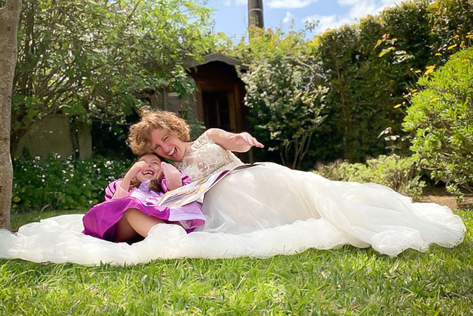 Rita Aleluia com criança, deitados na relva, durante um momento de gargalhada.