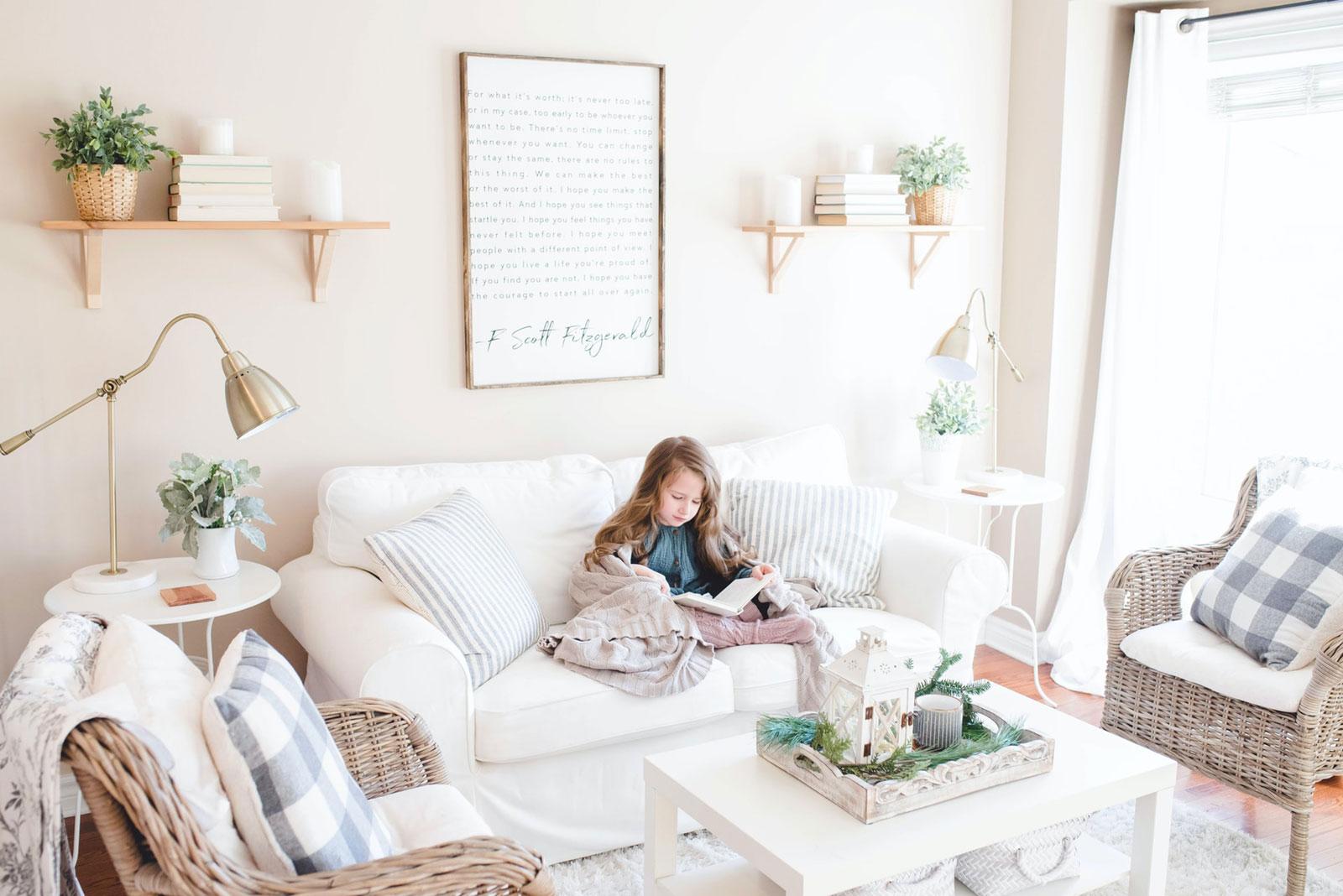 Criança a ler um livro, no sofá de uma sala muito iluminada através da janela.