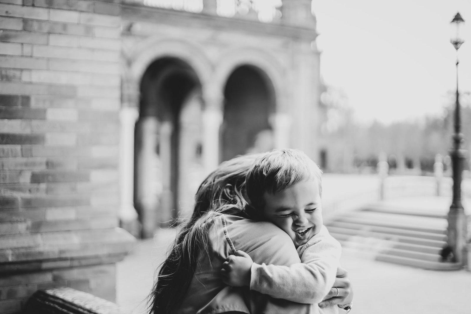 Duas crianças abraçam-se apertadamente, em ambiente citadino.