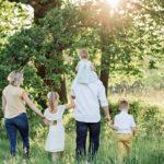 Família a passear num bosque, durante um dia com muito sol
