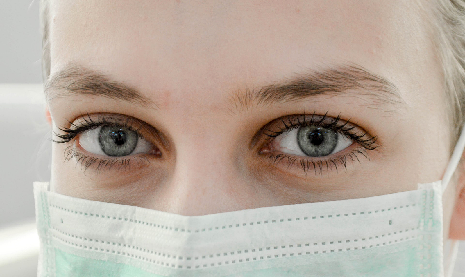 Rosto de rapariga loira, com olhos azuis e máscara cirúrgica.