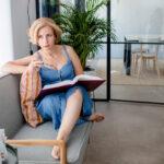Rita Aleluia a pensar, sentada num sofá e com enciclopédia de PNL sobre as pernas.