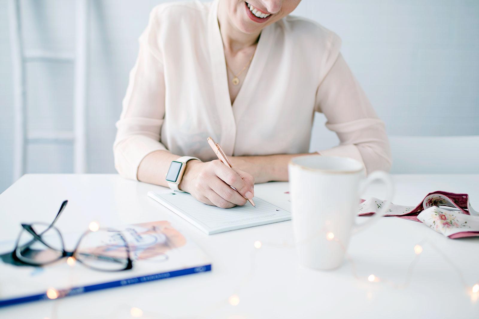 A escrever sobre uma secretária com um par de óculos e uma caneca