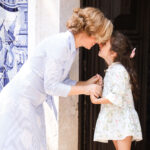 Rita Aleluia a segurar nas mãos de uma criança junto a uma igreja com azulejos azuis